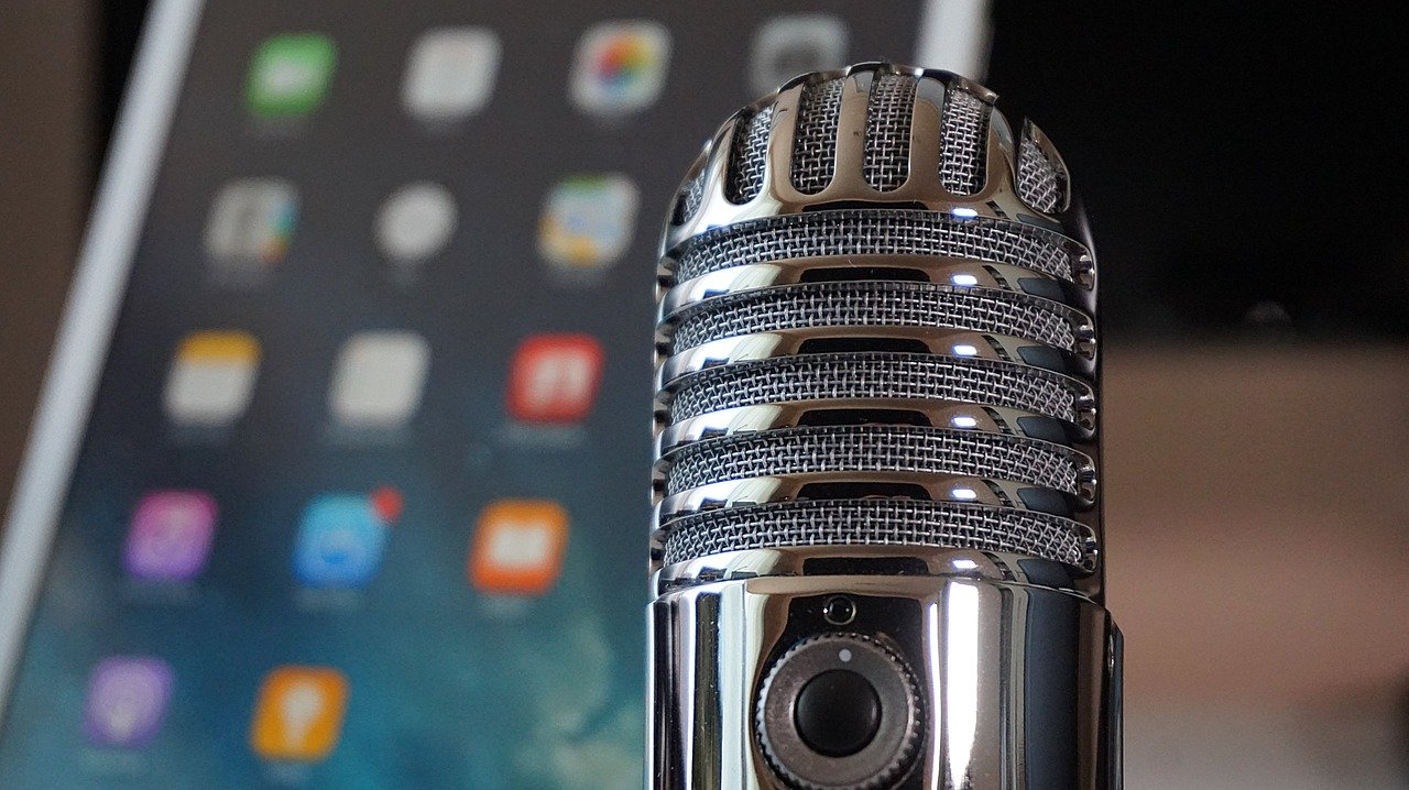 Image of a microphone with a smart phone or tablet in the background.